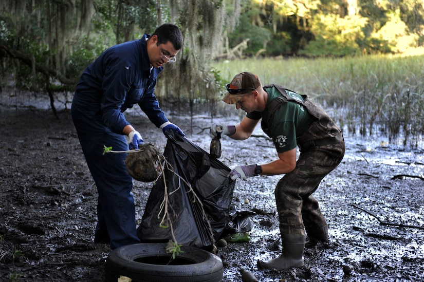 Chief Petty Officer Selectees James Holman and Matt Ryals, Naval Nuclear Power Training Command, collect debris from the Peas Hill Creek during a chief petty officer selectee community project Sept. 13, 2014, near James Island, S.C.. Chief selectees participate in COMREL projects as part of the CPO 365 Phase 2 training. The project was coordinated with Keep Charleston Beautiful, an organization that encourages local groups to volunteer for clean-up projects across the state by providing trash bags, gloves and any necessary supplies they might need. The chief selectees pinned on their anchors Sept. 16. (U.S. Air Force photo/Staff Sgt. Renae Pittman)