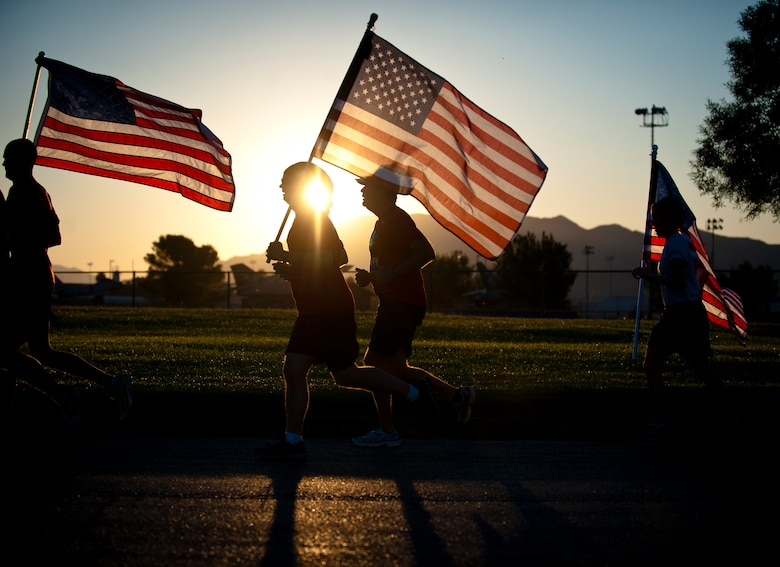 Members of Nellis Air Force Base run with the American flag Sept. 11, 2014, during the Old Glory Challenge at Nellis AFB, Nev. During the challenge, participants were charged with continuously running with the flag in 30-minute increments from 6:30 a.m. to 4:30 p.m. The goal of the event was to help participants remember the events of 9/11, honor those lost in defending freedom and tell the story of all who serve in defense of freedom. (U.S. Air Force photo/Staff Sgt. Siuta B. Ika)
