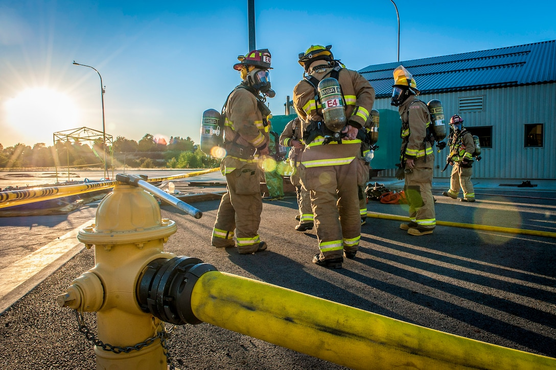 Fairchild Air Force Base firefighters join other regional firefighters as they don their self-contained breathing apparatuses to perform decontamination support near the spill zone of a hazardous materials incident Sept. 14, 2014, near the Washington-Idaho state line. Four firefighters, one technician and a variety of support staff as well as the base's mobile decontamination and rehabilitation unit joined two dozen other firefighters, trucks and equipment from Spokane regional fire districts in response to the incident. (U.S. Air Force photo/Staff Sgt. Benjamin W. Stratton)