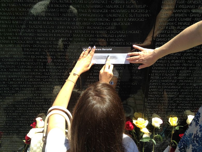 On Father's Day June 15, 2014, Caroline Kozak, the daughter of Maureen and Col. Raymond A. Kozak, the 512th Airlift Wing commander at Dover Air Force Base, Del., rubs a pencil across her grandfather's name on the Vietnam Veterans Memorial, in Washington, D.C. Her grandfather was an Air Force fighter pilot, who was shot down over North Vietnam in 1967 and was listed as missing in action until 1976, when he was declared killed in action, body not recovered. (Courtesy photo)