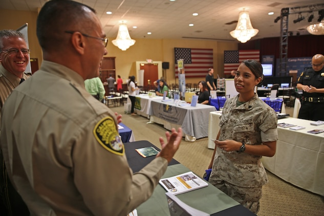 CAMP PENDLETON, Calif. - Marine Corps Base Camp Pendleton held a Hiring Our Heroes jobs summit at the Pacific Views Events Center here, Sept. 17-18, to provide service members, veterans and spouses with networking opportunities and improve their competitiveness in the workforce.     Lieutenant Ray Baez, an officer with the California Department of Corrections, discusses employment opportunities with Cpl. Jennifer Rolon, an intelligence analyst during the Career Fair portion of the summit.     Approximately 600 participants attended the event, which hosted 109 companies from a diverse field ranging from finance to the automotive industry.     (U.S. Marine Corps photo by Cpl. Shaltiel Dominguez)