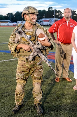 Tech. Sgt. Ismael Villegas, Special Tactics Training Squadron special tactics member, delivers the game football at Fort Walton Beach High School, Fort Walton Beach, Fla., Sept. 12, 2014. Fort Walton Beach High School hosted a military appreciation night, to pay tribute to the dedication of their local servicemen and women. . (U.S. Air Force photo/Airman 1st Class Jeff Parkinson)