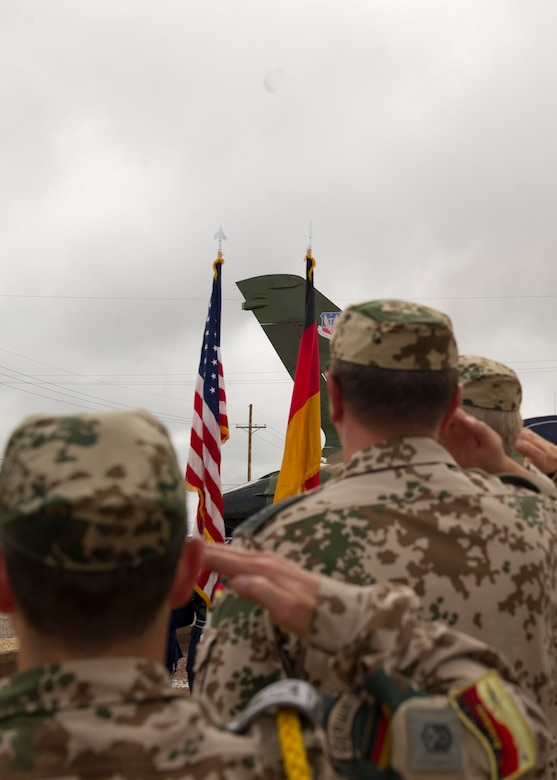 German Air Force members salute during the playing of both the German and United States National anthems. History was made Sep. 19, when a German Air Force static aircraft was unveiled in Heritage Park by Lt. Gen. Martin Schellis, German Air Force Operational Forces Command commander, and Col. Robert Kiebler, 49th Wing commander. The GAF Training Center and the Tornados are a significant part of military aviation operations in and around Holloman Air Force Base and White Sands Missile Range. (U.S. photo by Staff Sgt. E'Lysia Wray/ Released)