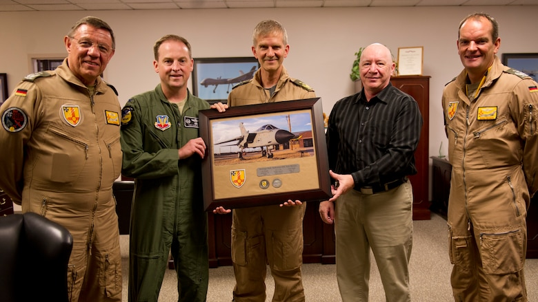 Colonel Robert Kiebler, 49th Wing commander and James Burrett, Wing historian, are presented with a plaque from Lt. Gen. Martin Schellis, German Air Force Operational Forces Command commander, Col. Heinz Ferkinghoff, German Air Force Flying Training Center commander, and Col. Armin Havenith, GAF FTC vice commander. History was made Sep. 19, when a German Air Force static aircraft was unveiled in Heritage Park by Schellis and Kiebler. The GAF Training Center and the Tornados are a significant part of military aviation operations in and around Holloman Air Force Base and White Sands Missile Range. (U.S. photo by Staff Sgt. E'Lysia Wray/ Released)