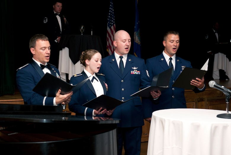 From left, Capt. Jason Parsons, Maj. Sarah Ford, Tech. Sgt. Jeff Achuff and Senior Airman James Baumgartner, all members of the 8th Space Warning Squadron singing group, perform at the Senior NCO Induction Ceremony Aug. 22, 2014, at the Heritage Eagle Bend Golf Club in Aurora, Colo. The group comprises 8th Space Warning Squadron members who perform the national anthem and other songs for military events and ceremonies. (U.S. Air Force photo by Airman 1st Class Samantha Saulsbury/Released)