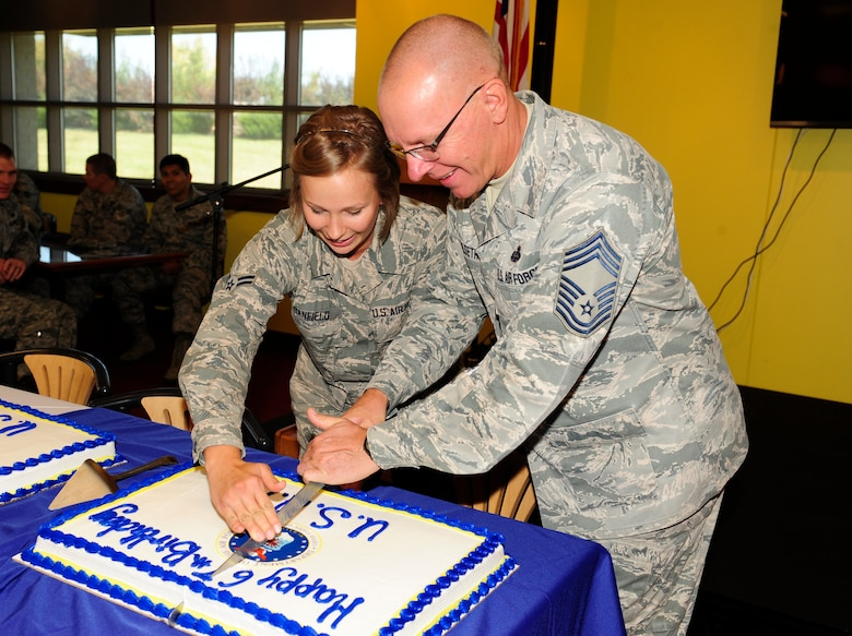 Airman 1st Class Tylar Stanfield, 460th Contracting Flight contracting specialist, left,and Chief Master Sgt. Richard Halseth, Aerospace Data Facility-Colorado senior enlisted leader, cut the cake during Team Buckley's 67th Air Force Birthday celebration Sept. 18, 2014, at Panther's Den on Buckley Air Force Base, Colo. Stanfield and Halseth were the Airmen with the least and most time in service, respectively, at the celebration. (U.S. Air Force photo by Airman 1st Class Samantha Saulsbury/Released)