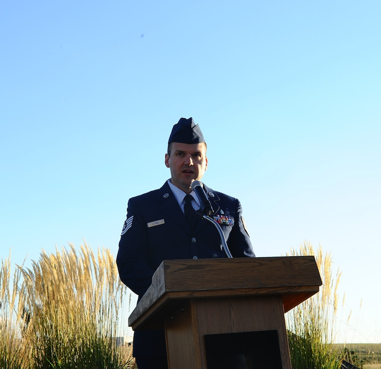 Tech. Sgt. Zach Coyner, 460th Medical Group non-commissioned officer in charge of physical therapy, speaks to Team Buckley members during the POW/MIA reveille ceremony Sept. 19, 2014, at the 460th Space Wing headquarters building on Buckley Air Force Base, Colo. The observance was held in honor of those who suffered as prisoners of war or are missing in action. (U.S. Air Force photo by Tech. Sgt. Rob Hazelett/Released)