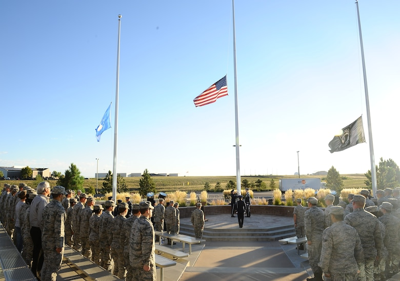 Team Buckley members watch as the American flag, Air Force flag and POW/MIA flags are secured by the Mile High Honor Guard during the National POW/MIA Recognition Day ceremony Sept. 19, 2014, at the 460th Space Wing headquarters building on Buckley Air Force Base, Colo. The observance was held in honor of those who suffered as prisoners of war or are missing in action. (U.S. Air Force photo by Tech. Sgt. Rob Hazelett/Released)
