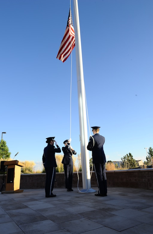 Mile High Honor Guard members lower the American flag to half-staff during the POW/MIA reveille ceremony Sept. 19, 2014, at the 460th Space Wing headquarters building on Buckley Air Force Base, Colo. According to the Defense Prisoner of War/Missing Personnel Office, more than 83,000 Americans are missing from World War II, the Korean War, the Cold War, the Vietnam War and the 1991 Gulf War. (U.S. Air Force photo by Tech. Sgt. Rob Hazelett/Released)