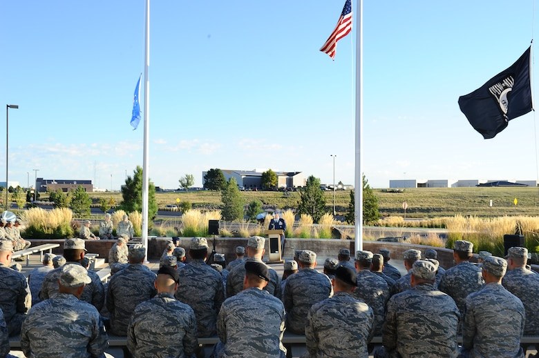 Team Buckley members listen to Col. Mitch Stratton, 460th Space Wing vice commander, during the POW/MIA reveille ceremony Sept. 19, 2014, at the 460th Space Wing headquarters building on Buckley Air Force Base, Colo. According to the Defense Prisoner of War/Missing Personnel Office, more than 83,000 Americans are missing from World War II, the Korean War, the Cold War, the Vietnam War and the 1991 Gulf War. (U.S. Air Force photo by Tech. Sgt. Rob Hazelett/Released)