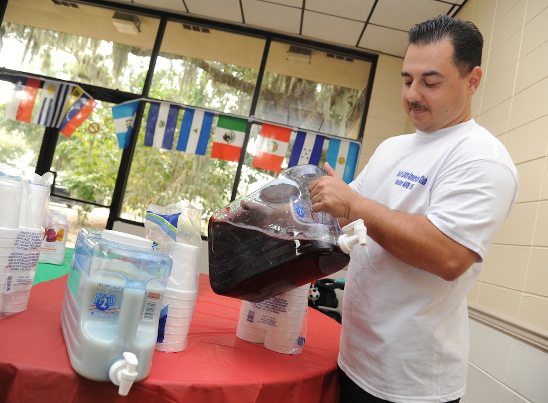 "Tech. Sgt. David Valencia, Keesler Latin-American Club president from the 81st Dental Squadron, mixes Jamaica, an herbal tea popular in Mexico, during the ""Arroz Con Pollo Extravaganza,"" Sept. 16, 2014, at marina park, Keesler Air Force Base, Miss.  The event included a variety of chicken and rice dishes and kicked off Hispanic Heritage Month. (U.S. Air Force photo by Kemberly Groue)"
