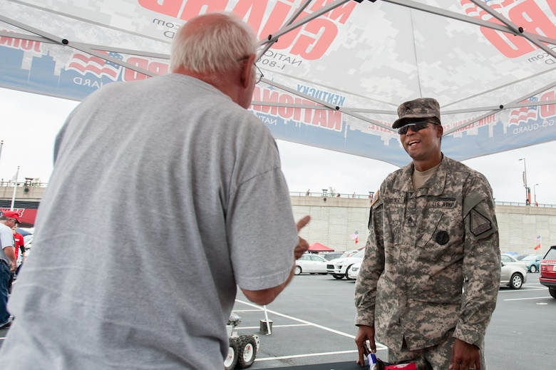 Army Staff Sgt. Michael Oliver, a recruiter for the Kentucky Army National Guard, speaks with a football fan outside Papa John's Cardinal Stadium in Louisville, Ky., prior to the University of Louisville – Murray State football game Sept. 6, 2014. The game, billed as Military Appreciation Day, began with a coin toss executed by Air Force Brig. Gen. Warren Hurst, the Kentucky National Guard's assistant adjutant general for Air and commander of the Kentucky Air National Guard. (U.S. Air National Guard photo by Maj. Dale Greer/Released)