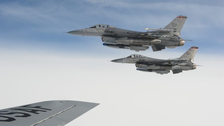 Two U.S. Air Force F-16 Fighting Falcon fighter aircraft from the 52nd Fighter Wing fly in formation beside the wing of a U.S. Air Force KC-135 Stratotanker during an aerial refueling mission at Spangdahlem Air Base, Germany, Sept 18, 2014. Six pilots from the 52nd FW participated in the refueling mission.  (U.S. Air Force photo by Airman 1st Class Luke J. Kitterman/Released)
