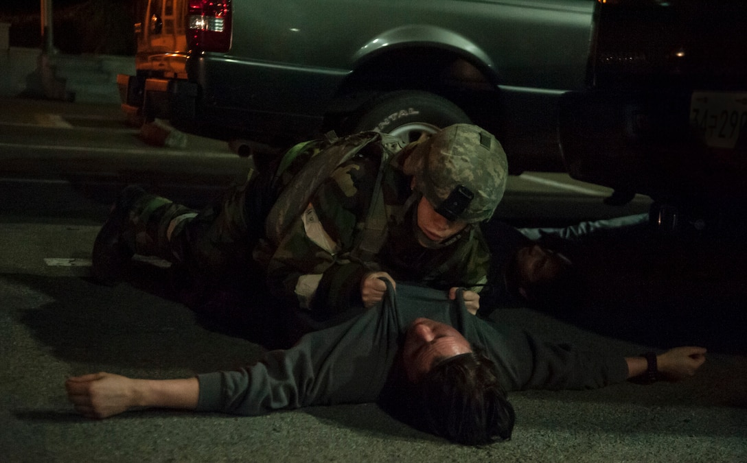 A 51st Security Forces Squadron member performs a roll over body check on a dead opposition forces member during Operational Readiness Exercise Beverly Midnight 14-4 Sept. 17, 2014, at Osan Air Base, Republic of Korea. This check is done to make sure the body is not wired with explosives. (U.S. Air Force photo by Senior Airman Matthew Lancaster)