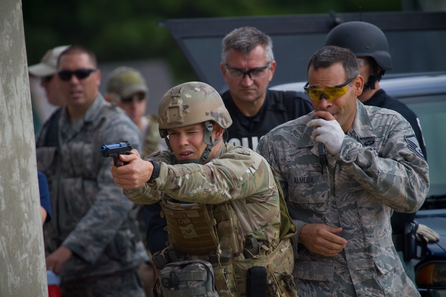 """U.S. Air Force Staff Sgt. Sean Dixon fires sim rounds while Master Sgt. Jose Almeida blows a whistle as a distraction during Tactical Combat Casualty Care training at the Anthony """"Tony"""" Canale Training Center in Egg Harbor Township, N.J., Sept. 19, 2014. The course, which was taught by Almeida, included students from the 177th Security Forces Squadron, the 227th Air Support Operations Squadron and numerous police officers from southern New Jersey. Dixon is a tactical air control party specialist from the 227th Air Support Operations Squadron. (U.S. Air National Guard photo by Tech. Sgt. Matt Hecht/Released)"""