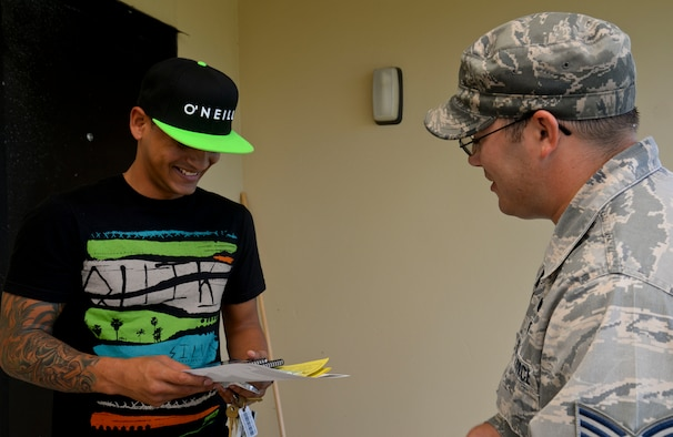 Senior Airman Thomas Hermansen, 36th Civil Engineering Emergency Management Flight, explains information from a tsunami preparedness handbook to Senior Airman Julio Santiago, 36th Force Support Squadron fitness specialist, Sept. 12, 2014, on Andersen Air Force Base, Guam. The Airmen went through base housing passing out information about natural disasters for National Preparedness Month. (U.S. Air Force photo by Staff Sgt. Robert Hicks/Released)