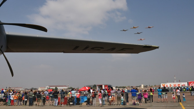 An aerial demonstration team flies over a crowd lined up to look inside a C-130J Super Hercules at the Africa Aerospace & Defence Expo at Waterkloof Air Force Base, South Africa, Sept. 20, 2014.  The C-130 was part of a total-force team of Guard, Reserve and active-duty Soldiers and Airmen at the expo. (U.S. Air Force photo/Staff Sgt. Travis Edwards)