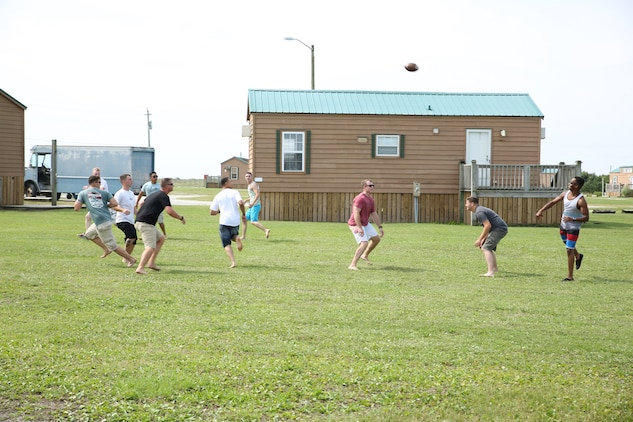 Marines and sailors with the Ground Combat Element Integrated Task Force play a game of football during the unit's beach bash family event at Onslow Beach. Sept. 19, 2014. Other activities during the event included volleyball, corn hole and basketball. From October 2014 to July 2015, the Ground Combat Element Integrated Task Force will conduct individual and collective skills training in designated combat arms occupational specialties in order to facilitate the standards based assessment of the physical performance of Marines in a simulated operating environment performing specific ground combat arms tasks. (U.S. Marine Corps photo by Cpl. Paul S. Martinez/Released)