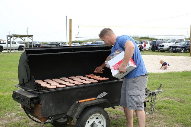 Sgt. Michael Comerford, ground radio repairman, Ground Combat Element Integrated Task Force, cooks hamburgers and hot dogs during the unit's beach bash family event at Onslow Beach. Sept. 19, 2014. The bash served as the unit's first family event. From October 2014 to July 2015, the Ground Combat Element Integrated Task Force will conduct individual and collective skills training in designated combat arms occupational specialties in order to facilitate the standards based assessment of the physical performance of Marines in a simulated operating environment performing specific ground combat arms tasks. (U.S. Marine Corps photo by Cpl. Paul S. Martinez/Released)