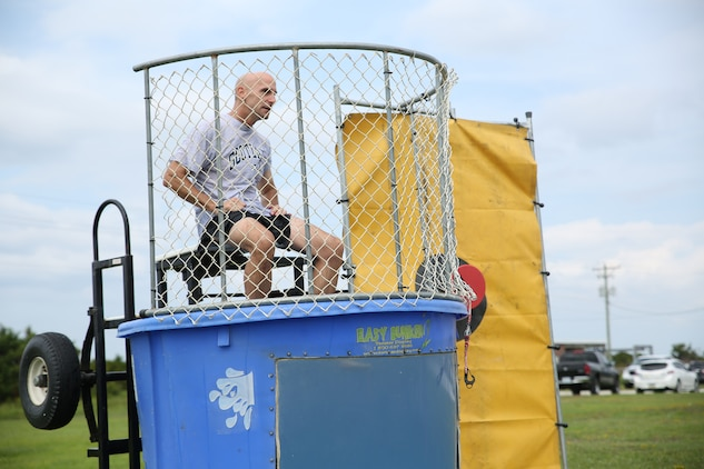 Col. Matthew G. St. Clair, commanding officer, Ground Combat Element Integrated Task Force, sits in the dunk tank during the unit's beach bash family event at Onslow Beach. Sept. 19, 2014. St. Clair, along with other officers in the unit, was dunked by Marines. From October 2014 to July 2015, the Ground Combat Element Integrated Task Force will conduct individual and collective skills training in designated combat arms occupational specialties in order to facilitate the standards based assessment of the physical performance of Marines in a simulated operating environment performing specific ground combat arms tasks. (U.S. Marine Corps photo by Cpl. Paul S. Martinez/Released)
