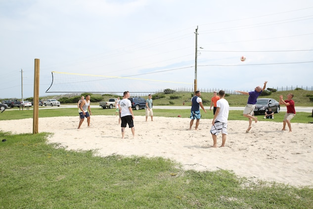Marines and sailors with the Ground Combat Element Integrated Task Force play a game of volleyball during the unit's beach bash family event at Onslow Beach. Sept. 19, 2014. Other activities during the event included basketball, corn hole and football. From October 2014 to July 2015, the Ground Combat Element Integrated Task Force will conduct individual and collective skills training in designated combat arms occupational specialties in order to facilitate the standards based assessment of the physical performance of Marines in a simulated operating environment performing specific ground combat arms tasks. (U.S. Marine Corps photo by Cpl. Paul S. Martinez/Released)