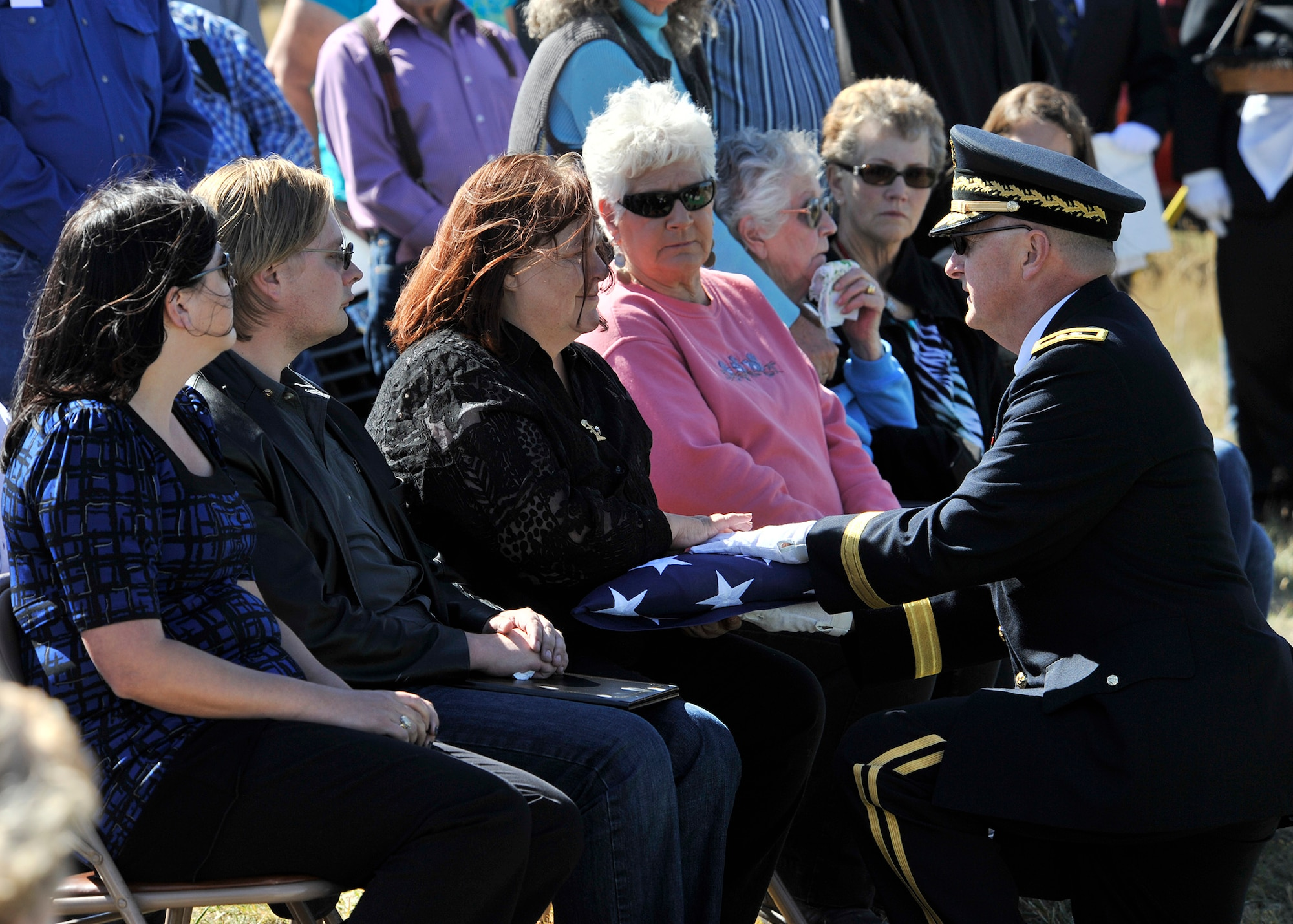 Maj. Gen. Matthew Quinn, l, presents the folded flag from the casket of Army Air Forces 1st Lt. William D. Bernier to Sandi Jones, Bernier's niece, Sept. 19, 2014,  at Augusta Cemetery, Mont. Bernier was killed in action over New Guinea during WWII, and his remains were positively identified earlier this year. Quinn is the adjutant general of the Montana National Guard. (Air Force photo/John Turner)