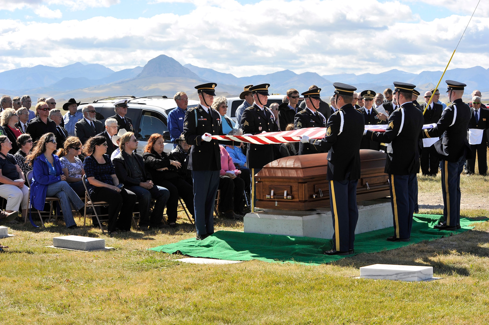 Soldiers from the Montana Army National Guard honor guard elevate an American flag over the casket containing Army Air Forces 1st Lt. William D. Bernier Sept. 19, 2014,  at Augusta Cemetery, Mont. Bernier was killed in action over New Guinea during WWII, and his remains were positively identified earlier this year. (Air Force photo/John Turner)