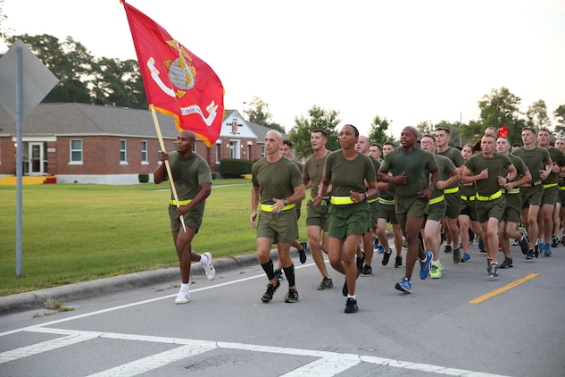 Col. Matthew G. St. Clair, commanding officer, Ground Combat Element Integrated Task Force, and Sgt. Maj. Robin C. Fortner, sergeant major, GCEITF, lead the task force to the finish line of a run aboard Marine Corps Base Camp Lejeune, North Carolina, Sept. 19, 2014. The run was in celebration of the uncasing of the units organizational colors.  From October 2014 to July 2015, the Ground Combat Element Integrated Task Force will conduct individual and collective skills training in designated combat arms occupational specialties in order to facilitate the standards based assessment of the physical performance of Marines in a simulated operating environment performing specific ground combat arms tasks. (U.S. Marine Corps photo by Cpl. Paul S. Martinez/Released)