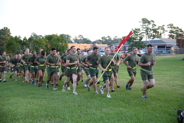 Capt. Raymond Kaster, commanding officer, Company A, Ground Combat Element Integrated Task Force, leads Marines to the finish line of a run aboard Marine Corps Base Camp Lejeune, North Carolina, Sept. 19, 2014. The run was in celebration of the uncasing of the units organizational colors.  From October 2014 to July 2015, the Ground Combat Element Integrated Task Force will conduct individual and collective skills training in designated combat arms occupational specialties in order to facilitate the standards based assessment of the physical performance of Marines in a simulated operating environment performing specific ground combat arms tasks. (U.S. Marine Corps photo by Cpl. Paul S. Martinez/Released)