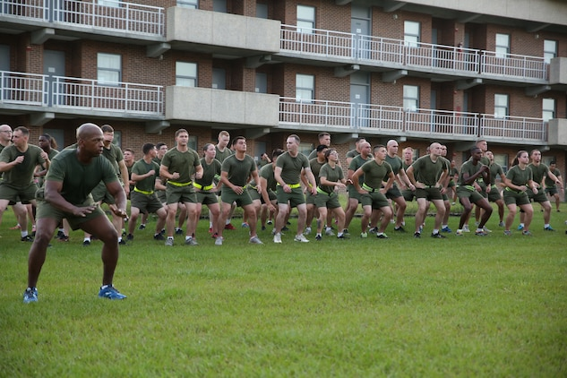 1st Sgt. Jonathan Borders, first sergeant, Headquarters and Service Company, Ground Combat Element Integrated Task Force, conducts exercises with Marines and sailors after a run aboard Marine Corps Base Camp Lejeune, North Carolina, Sept. 19, 2014. The run was in celebration of the uncasing of the units organizational colors. From October 2014 to July 2015, the Ground Combat Element Integrated Task Force will conduct individual and collective skills training in designated combat arms occupational specialties in order to facilitate the standards based assessment of the physical performance of Marines in a simulated operating environment performing specific ground combat arms tasks. (U.S. Marine Corps photo by Cpl. Paul S. Martinez/Released)