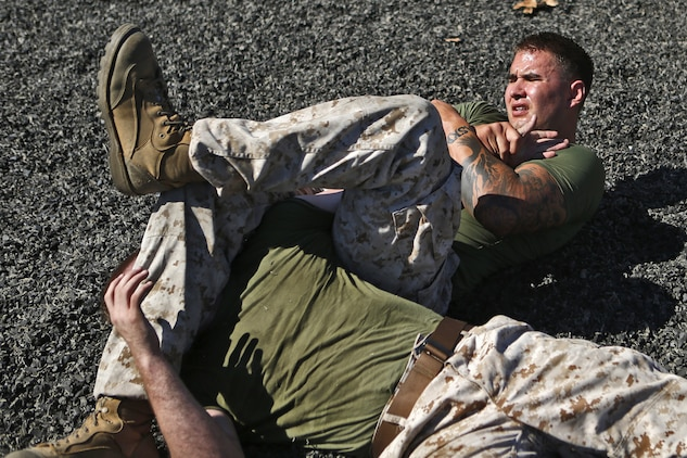 Lance Cpl. Sheldon D. Vogt, right, a machinegunner with 2nd Battalion, 1st Marine Regiment, 1st Marine Division, attempts an armbar on Cpl. Sean Cooley, left, team captain of the Headquarters and Support Battalion, Marine Corps Base Camp Pendleton, Marine Corps Installations - West, while training to prepare for the upcoming Commanding General's Cup grappling tournament at the Paige Fieldhouse, Oct. 29.