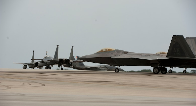 A U.S. Air Force F-15C Eagle and F-22 Raptor taxi during Valiant Shield 2014 in anticipation of operations in a joint airspace environment, Sept. 16, 2014, Andersen Air Force Base, Guam. Valiant Shield is a U.S.-only exercise, integrating an estimated 18,000 U.S. Navy, Air Force, U.S. Army and U.S. Marine Corps personnel, more than 200 aircraft and 19 surface ships, offering real-world joint operational experience to develop capabilities that provide a full range of options to defend U.S. interests and those of its allies and partners. (U.S. Air Force Photo by Staff Sgt. William Banton/Released)