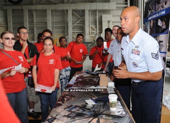 Staff Sgt. Clifford Roy, local recruiter from the 331st Recruiting Squadron, Maxwell Air Force Base, Ala., provides information at an Air Force recruitment booth to Biloxi High School Junior ROTC students during the STEM (science, technology, engineering and mathematics) Diversity Outreach Day Sept. 19, 2014, at the fuel cell hangar, Keesler Air Force Base, Miss.  The event consisted of 10 Mississippi gulf coast high school JROTC units visiting informative booths about Air Force opportunities and accession requirements with an emphasis on STEM.  (U.S. Air Force photo by Kemberly Groue)