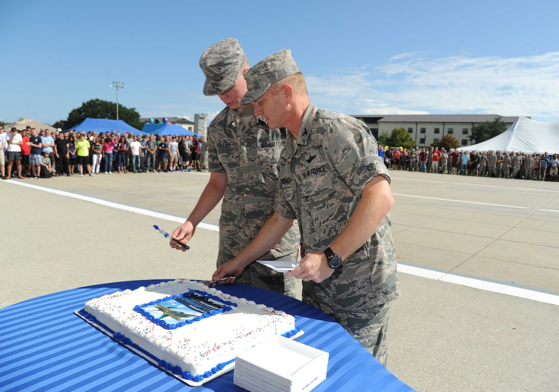 Airman Basic Anthony Salley, 338th Training Squadron and the youngest Airman at Keesler, assists Col. Dennis Scarborough, 81st Training Wing vice commander, with cutting the birthday cake during the Air Force's 67th birthday celebration Sept. 19, 2014, Keesler Air Force Base, Miss. The event also included music, games, contests and food.  (U.S. Air Force photo by Kemberly Groue)