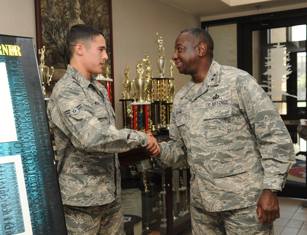 """Airman 1st Class Joshua Marsh, 336th Training Squadron, receives a coin from Maj. Gen. Mark Brown, 2nd Air Force commander, following Marsh's briefing on the """"Get it"""" discipline corner poster at Thomson Hall during a two-day immersion tour of the base Sept. 16-17, 2014, Keesler Air Force Base, Miss.  The purpose of the tour was to learn the integration of the base's mission, operations and personnel.  Brown also toured the 81st Medical Group, 81st Mission Support Group and held an all call. (U.S. Air Force photo by Kemberly Groue)"""