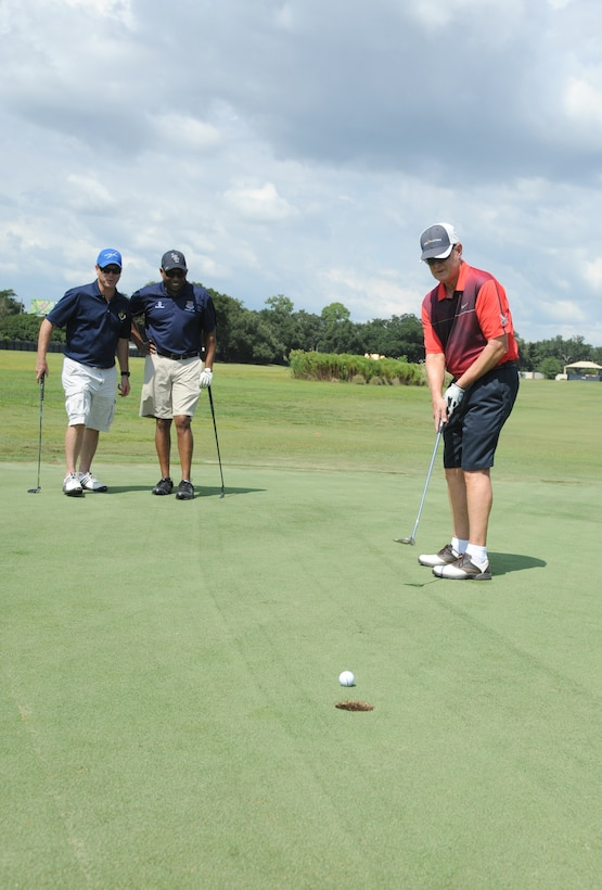 Chief Master Sgts. David Staton, 2nd Air Force command chief, and Farrell Thomas, 81st Training Wing command chief, watch retired Col. Bob Neal putt the ball into hole number 4 during the Don Wylie Memorial Annual Golf Tournament Sept. 19, 2014, at the Bay Breeze Golf Course, Keesler Air Force Base, Miss.  Keesler defeated the Biloxi Bay Chamber. (U.S. Air Force photo by Kemberly Groue)
