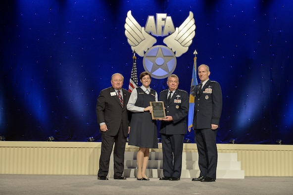 Capt. Stephanie Doane, Mountain Home Air Force Base nurse, is awarded the Air Force Association Juanita Redmond Award by George Muellner, AFA Chairman, Lt. Gen. (Dr.) Thomas Travis, Air Force Surgeon General, and Gen. Mike Hostage, Air Combat Command Commander, on Sept. 15, 2014 at the Gaylord Convention Center in National Harbor, Md.    The Juanita Redmond Award is awarded to an Air Force nurse who has provided a significant contribution to health care of an Air Force individual or family, excellence in clinical nursing or improvment in nursing care.  (Courtesy Photo)