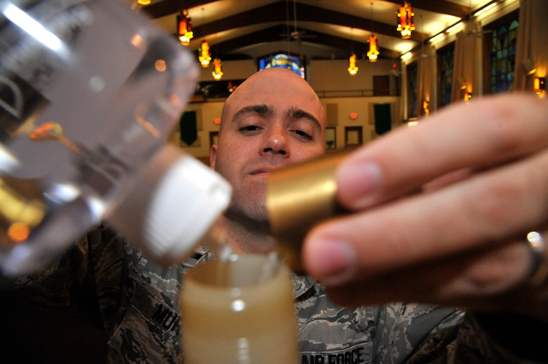 U.S. Air Force Staff Sgt. Ronald Murray, 509th Bomb Wing chaplain assistant, prepares for Mass by filling the altar candles at Whiteman Air Force Base, Mo., Sept. 3, 2014. Chaplain assistants prepare the chapel throughout the week to ensure chaplains are able to conduct their services. (Air Force photo by Airman 1st Class Keenan Berry/Released)