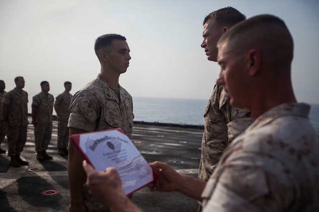U.S. Marine Corps Cpl. Will Demarest, left, Battalion Landing Team 1st Battalion, 6th Marine Regiment, 22nd Marine Expeditionary Unit (MEU), assault amphibious vehicle crewman and native of Glen Mills, Pa., receives a certificate of commendation as for achieving the title of honor graduate for a corporals course aboard the amphibious dock landing ship USS Gunston Hall (LSD 44). The 22nd MEU is deployed with the Bataan Amphibious Ready Group as a theater reserve and crisis response force throughout U.S. Central Command and the U.S. 5th Fleet area of responsibility. (U.S. Marine Corps photo by Sgt. Austin Hazard/Released)