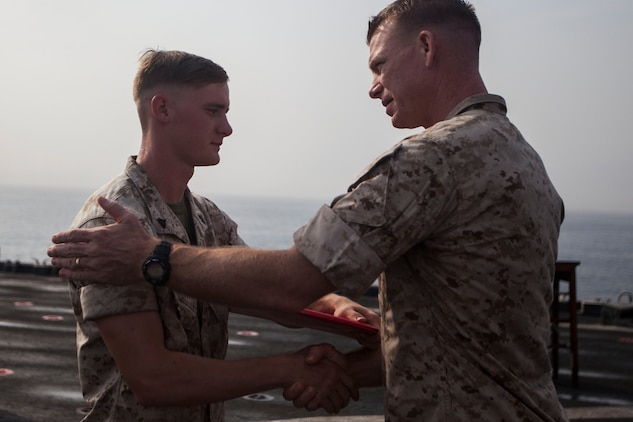 U.S. Marine Corps Cpl. Korey Bryant, left, Combat Logistics Battalion 22, 22nd Marine Expeditionary Unit (MEU), assault amphibious recovery vehicle crewman and native of Bladenboro, N.C., receives his diploma during a corporals course graduation ceremony aboard the amphibious dock landing ship USS Gunston Hall (LSD 44). The 22nd MEU is deployed with the Bataan Amphibious Ready Group as a theater reserve and crisis response force throughout U.S. Central Command and the U.S. 5th Fleet area of responsibility. (U.S. Marine Corps photo by Sgt. Austin Hazard/Released)