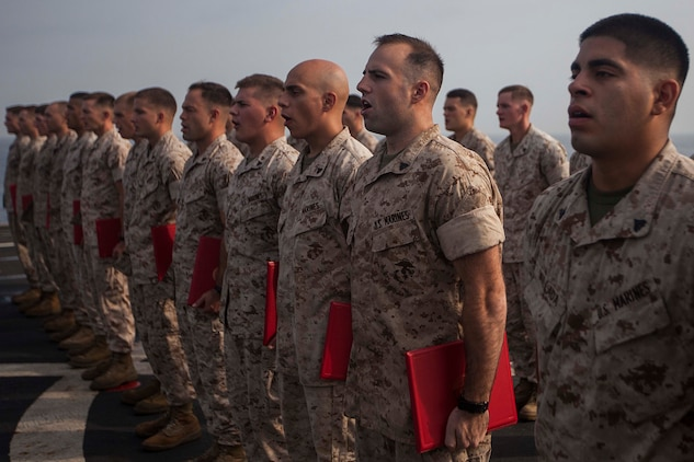 U.S. Marines sing the Marines' Hymn during a corporals course graduation ceremony aboard the amphibious dock landing ship USS Gunston Hall (LSD 44). The 22nd MEU is deployed with the Bataan Amphibious Ready Group as a theater reserve and crisis response force throughout U.S. Central Command and the U.S. 5th Fleet area of responsibility. (U.S. Marine Corps photo by Sgt. Austin Hazard/Released)