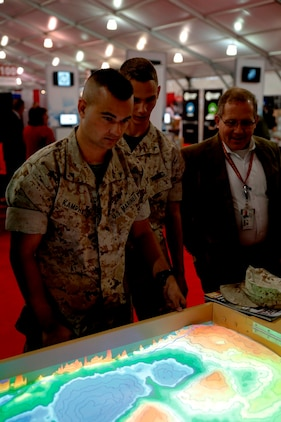 Modern Day Marine attendees look down at the contour map projected onto the sand of the Augmented Reality Sand Table on Marine Corps Base Quantico, Va., on Sept. 23. The ARES combines readily available and relatively inexpensive commercial off-the-shelf technology to make one of the battlefield's oldest technologies like new.