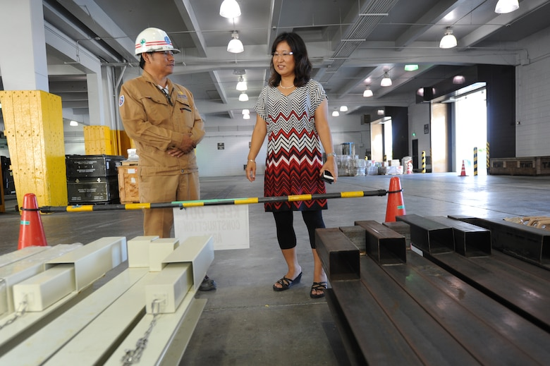 John Guadalupe, 733rd Air Mobility Squadron quality control manager (left), speaks with Keiko Okuhara, 733rd AMS facility manager (right), about reordering and replacing of the typhoon bars seen below on Kadena Air Base, Japan, Sept. 24, 2014. One of the 733rd AMS's responsibilities is the building updates to include safety such as these reinforcing bars for the roll down doors. (U.S. Air Force photo by Airmen 1st Class Zackary A. Henry/Released)
