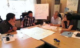 Far East District employees discussing district's mission and vision in a small group.