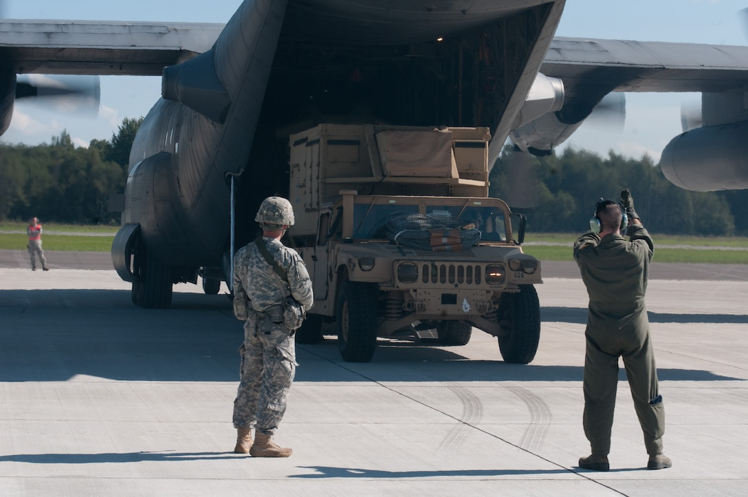 Air Force Tech. Sgt. Paul Jones (right), a loadmaster with the Kentucky Air National Guard's 123rd Airlift Wing, directs the offloading of cargo from a Kentucky C-130 Hercules as the aircraft waits to depart an airfield in Latvia on Sept. 6, 2014, during Operation Saber Junction. The 123rd participated in the training exercise along with five other Air Guard units and troops from 17 NATO countries. (U.S. Air National Guard photo by 2nd Lt. James W. Killen)