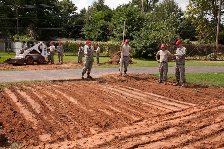 Members of the 307th RED HORSE and 307th Civil Engineer Squadron prepare ground for two of three additional fitness areas being built along a running trail on Barksdale Air Force Base, La., Sept. 8, 2014. Exercise equipment to be installed on the pads have smart phone capabilities, and will allow the athlete an opportunity to watch videos on how to properly use each piece of equipment and several examples of different exercises. (U.S. Air Force photo by Master Sgt. Jeff Walston/Released)