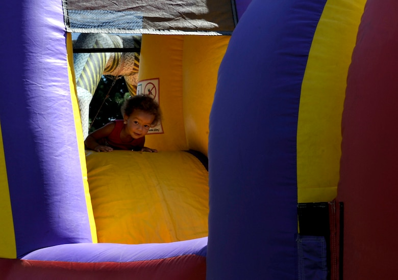PETERSON AIR FORCE BASE, Colo. - Tiana Sarrett, 2, makes her way through the inflatable obstacle course at the World Wide Day of Play held at Patriot Park Sept. 20 and hosted by the RP Lee Youth Center. Worldwide Day of Play is an annual event designed to encourage children and parents to turn off the television and get outside and play. The event had many activities for kids to enjoy, including a climbing wall, inflatable games and obstacle courses, and healthy snacks. (U.S. Air Force photo/Airman 1st Class Rose Gudex)