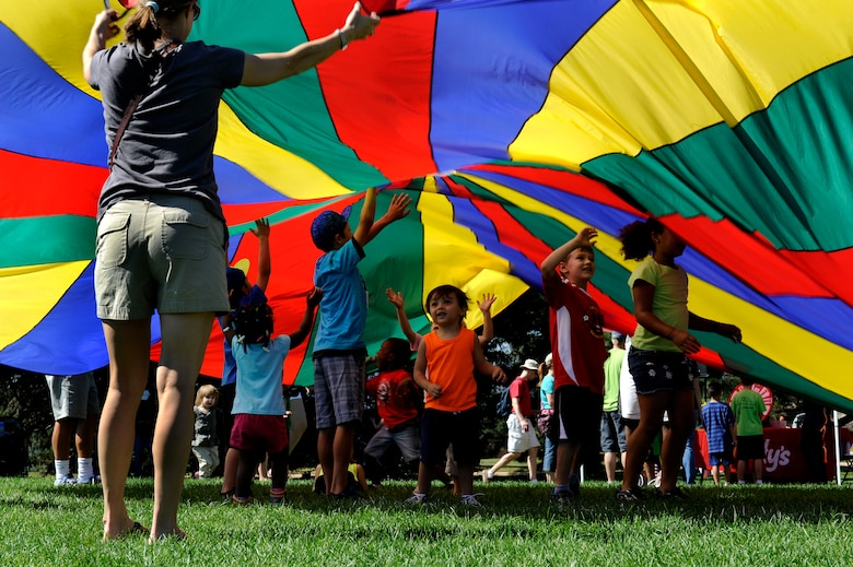 PETERSON AIR FORCE BASE, Colo. - Children play under the giant parachute at the World Wide Day of Play held at Patriot Park Sept. 20 and hosted by the RP Lee Youth Center. Worldwide Day of Play is an annual event designed to encourage children and parents to turn off the television and get outside and play. (U.S. Air Force photo/Airman 1st Class Rose Gudex)