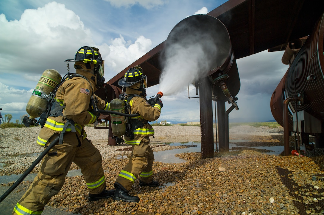 Staff Sgt. Phillip Daniels (left) and Senior Airman Mark Dunford, 49th Civil Engineer Squadron Fire Protection Flight firefighters extinguish a simulated number three engine fire during capability demonstration of the P-34 Rapid Intervention Vehicle at Holloman Air Force Base, N.M., Sept. 21, 2014. The RIV is three times more cost effective than the conventional firefighting vehicles. (U.S. Air Force photo by Airman 1st Class Aaron Montoya)