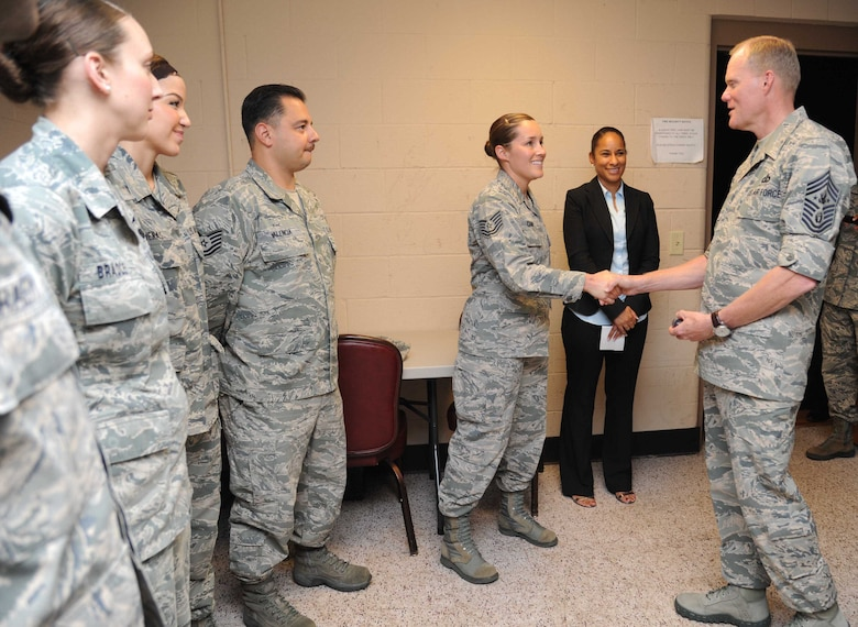 Chief Master Sgt. of the Air Force James A. Cody recognizes Tech. Sgt. Christina Camp with a coin as her supervisor, Desirae McIntyre, stands by Sept. 23, 2014, at the Welch Theater on Keesler Air Force Base, Miss. The purpose of the two-day visit was to thank Keesler AFB members and further understand the various missions here, including 2nd Air Force, 81st Training Wing and the 403rd Wing. Camp is assigned to the 334th Training Squadron. (U.S. Air Force photo/Kemberly Groue)